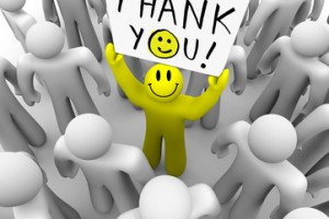 A smiley-faced yellow person stands out in a crowd holding a sign reading Thank You